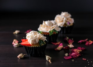 white and pink flowers on black cupcake stand