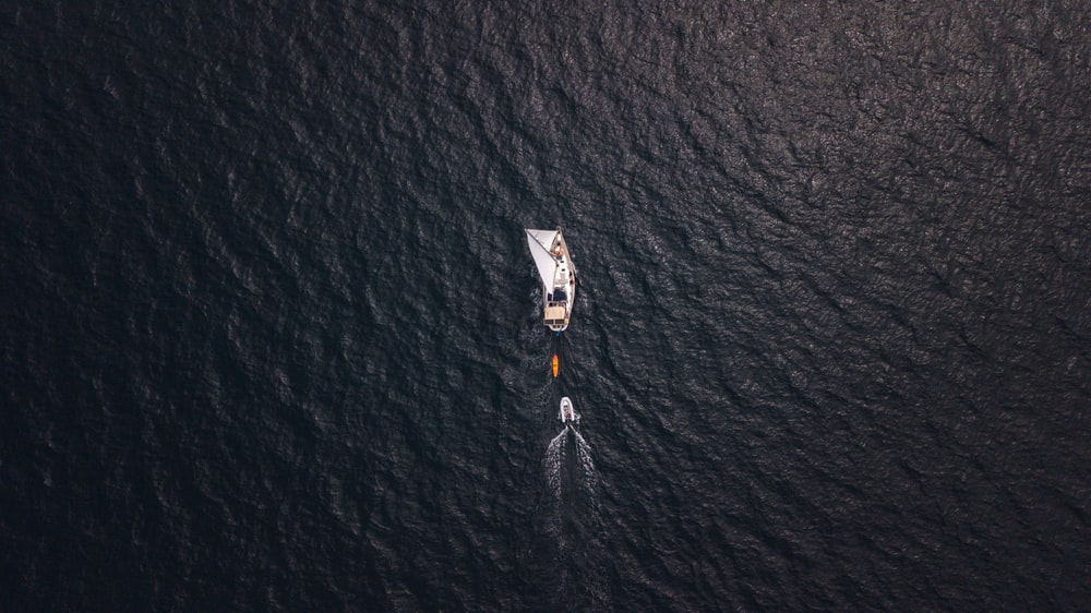 aerial view of person in white shirt and black pants on body of water during daytime