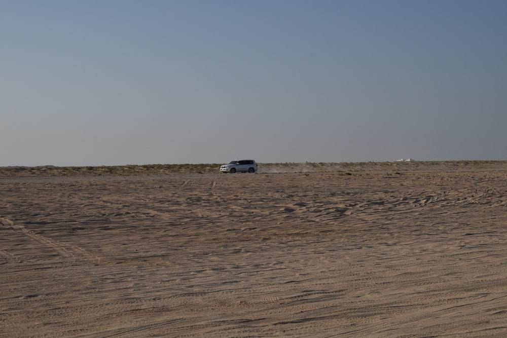 white car on brown sand
