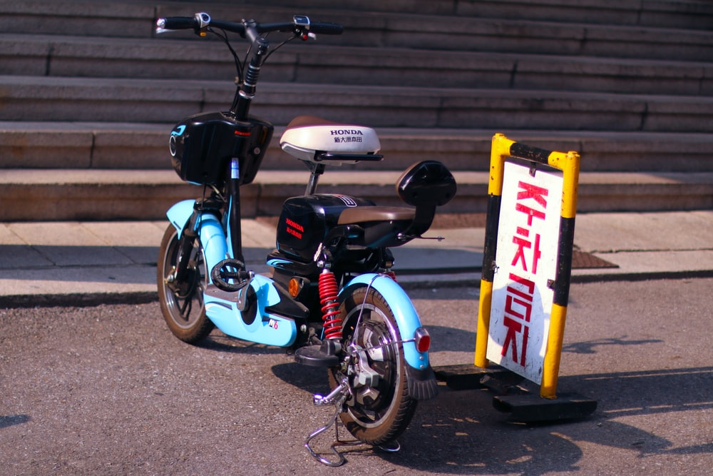 blue and white motorcycle parked beside pedestrian lane
