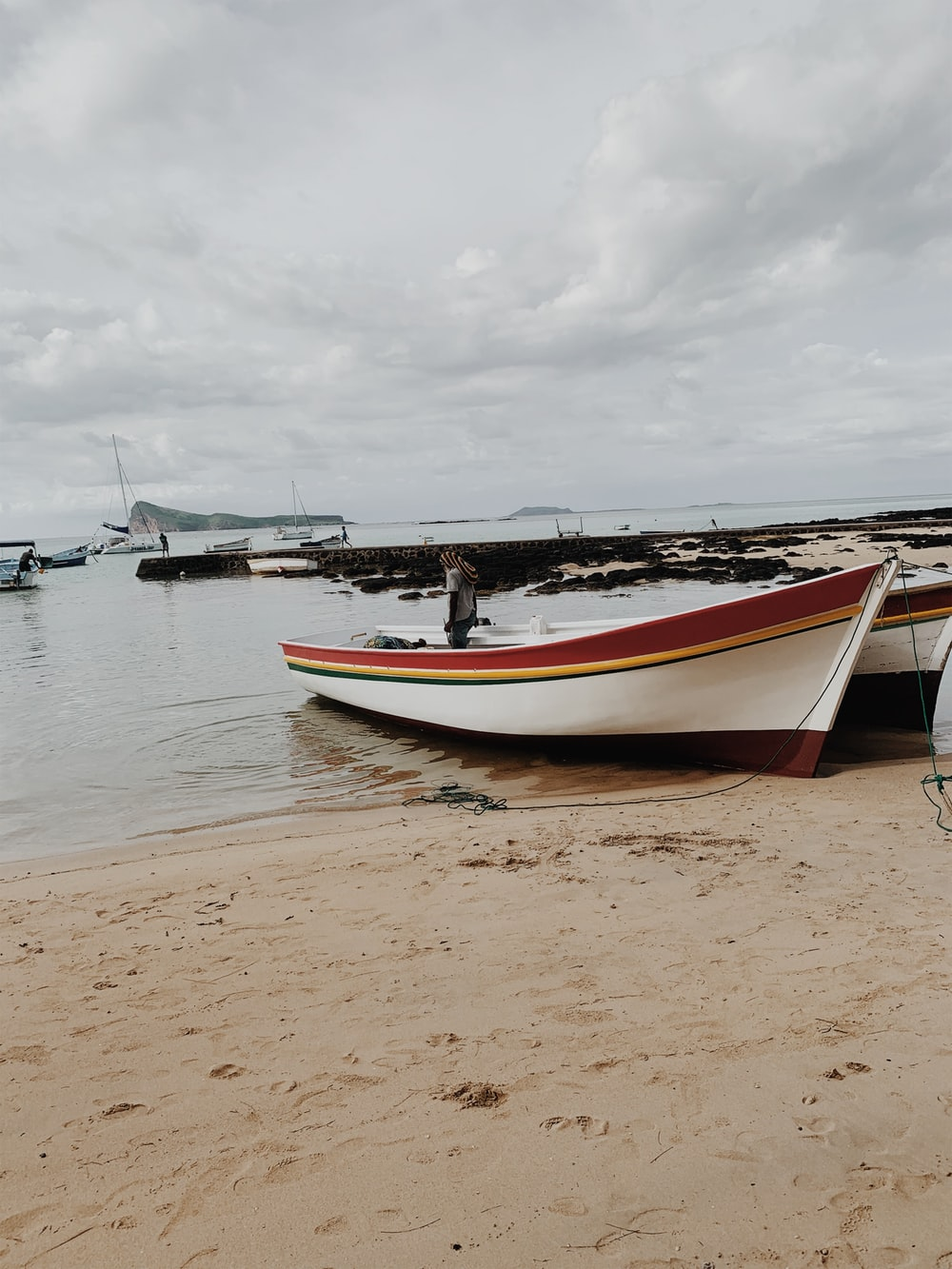 white and blue boat on brown sand during daytime