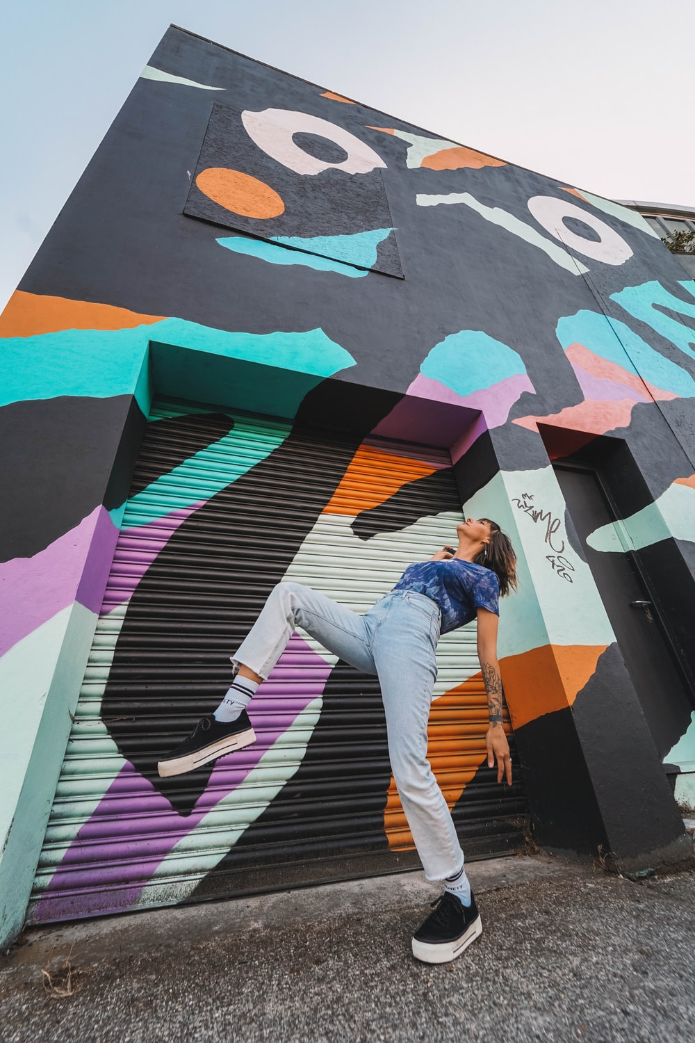 woman in blue denim jacket and white pants standing on wall with graffiti during daytime