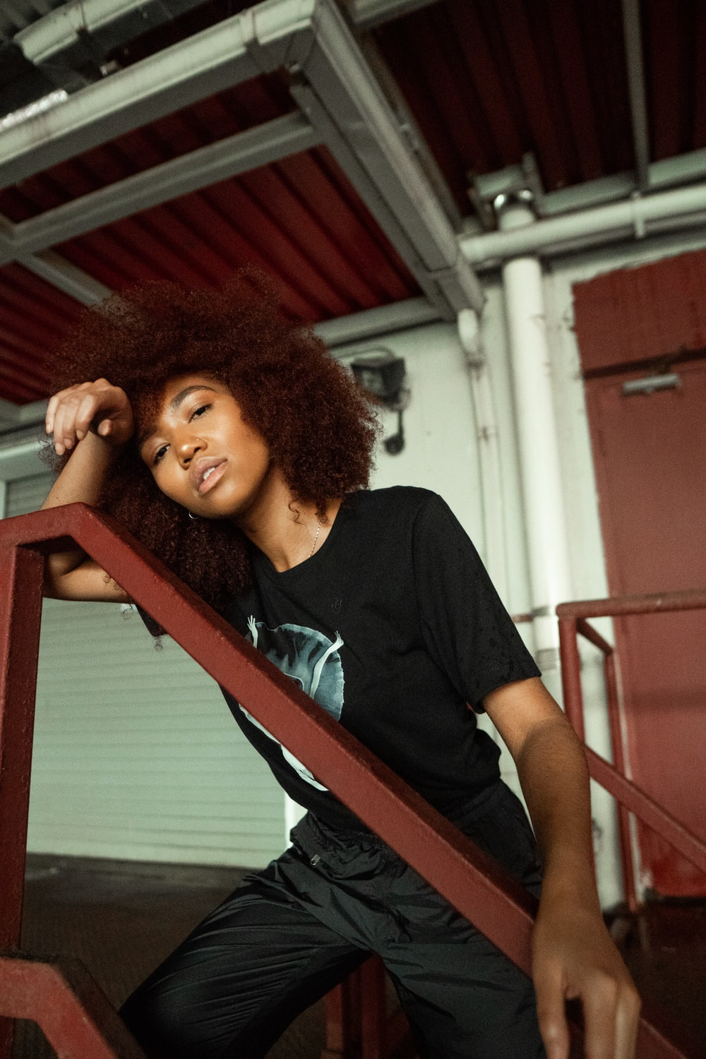 woman in black crew neck t-shirt leaning on red metal railings