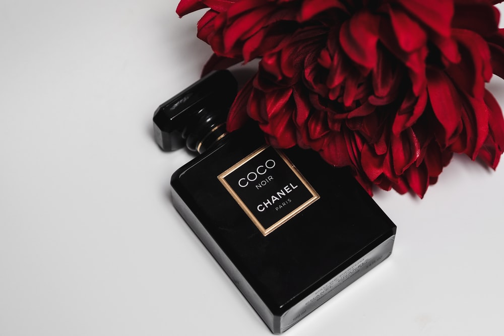 black and gold perfume bottle beside red rose