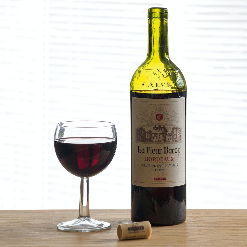 green glass bottle beside clear wine glass