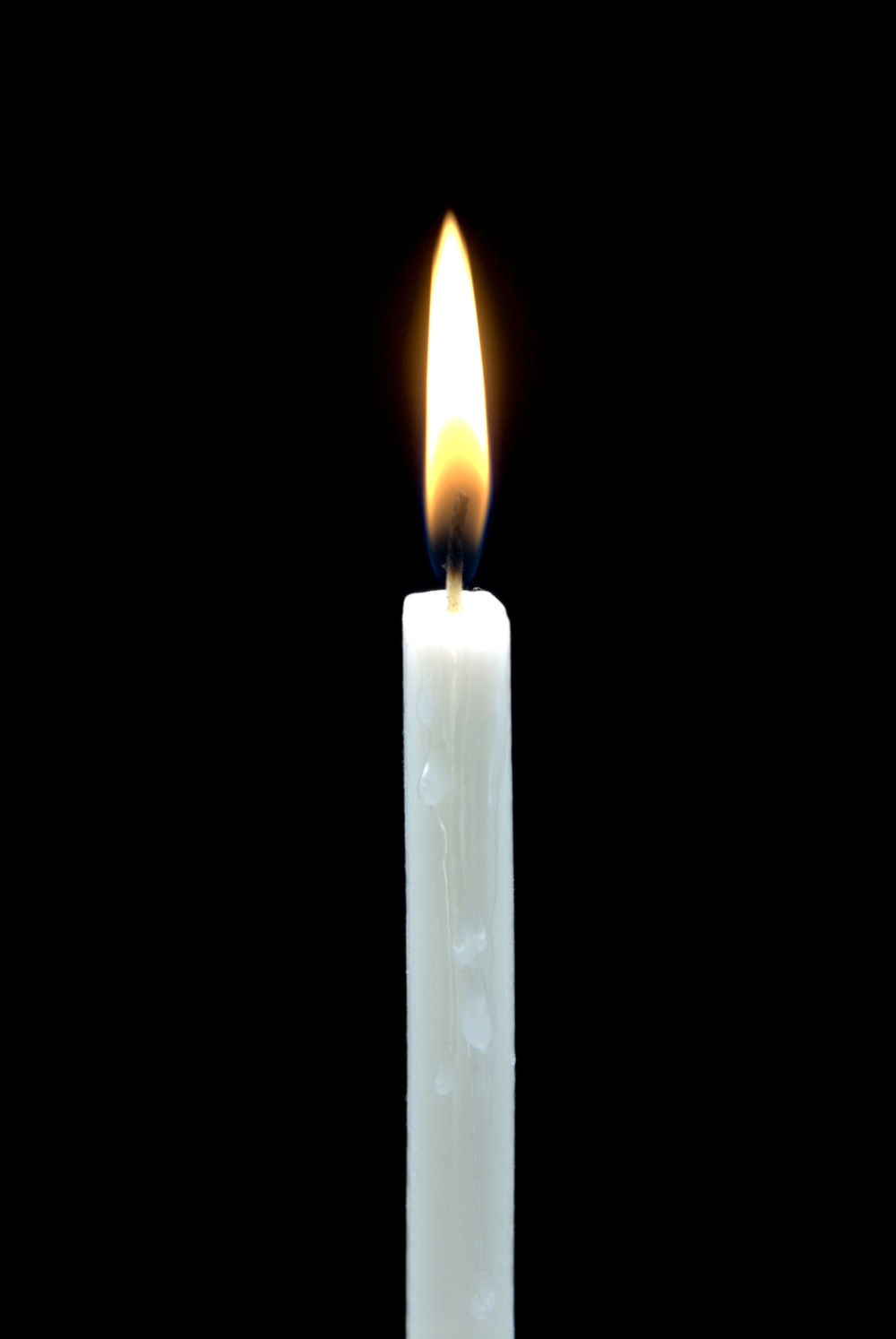 white lighted candle in dark room