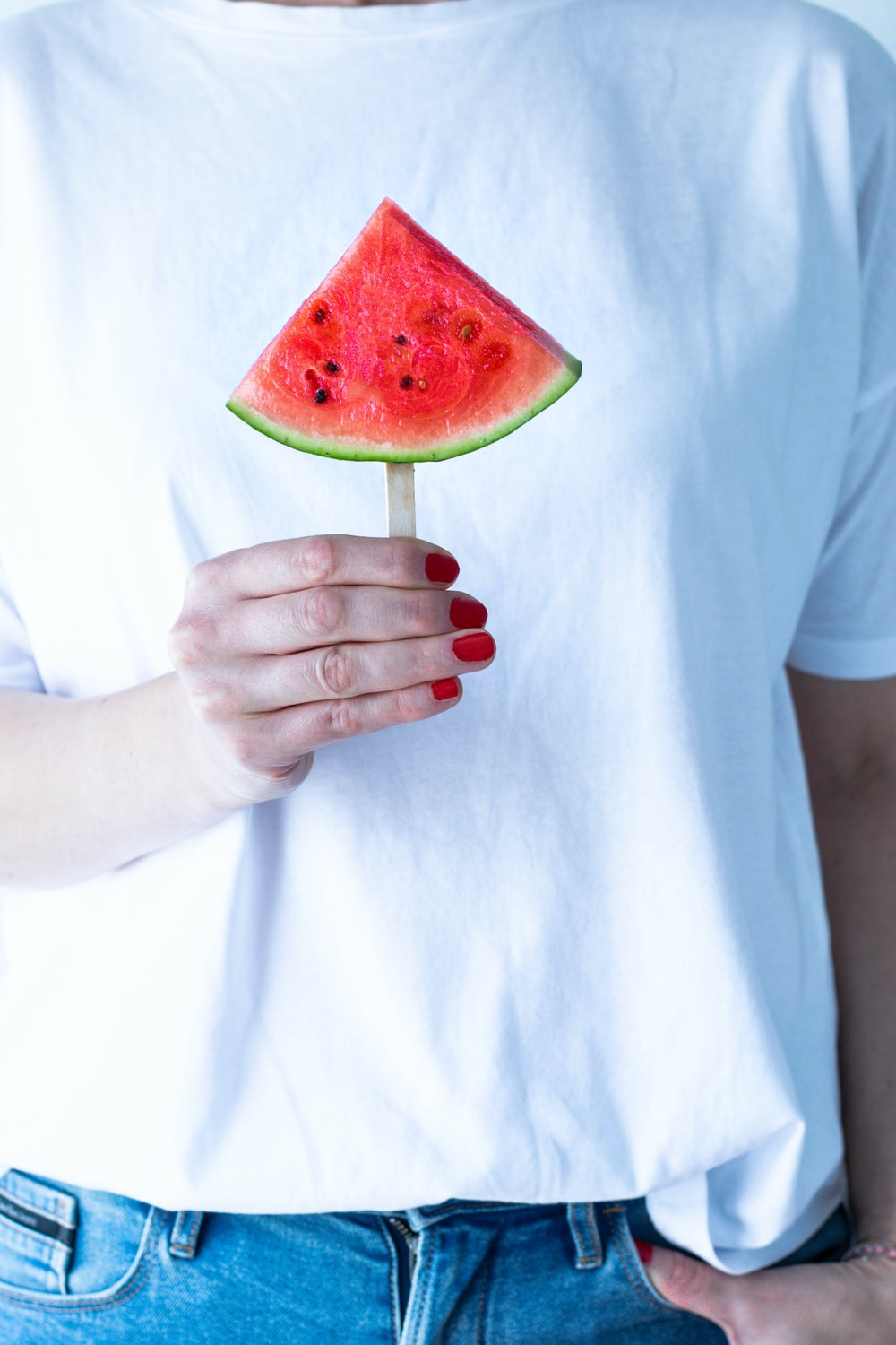 person in white crew neck t-shirt holding watermelon