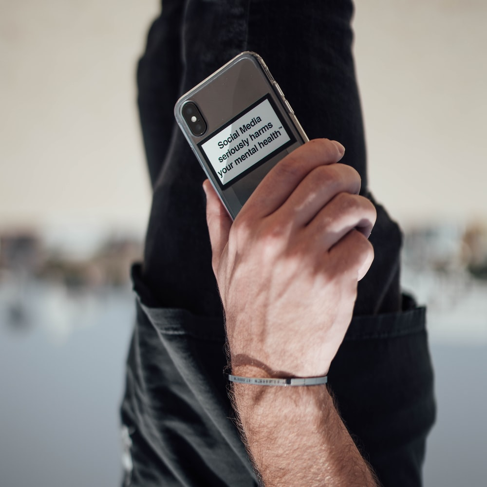 person holding black iphone 4