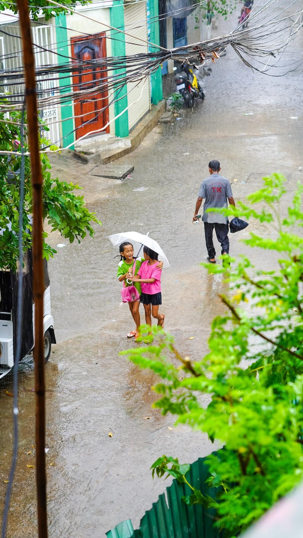 2 boys walking on sidewalk holding umbrella during daytime