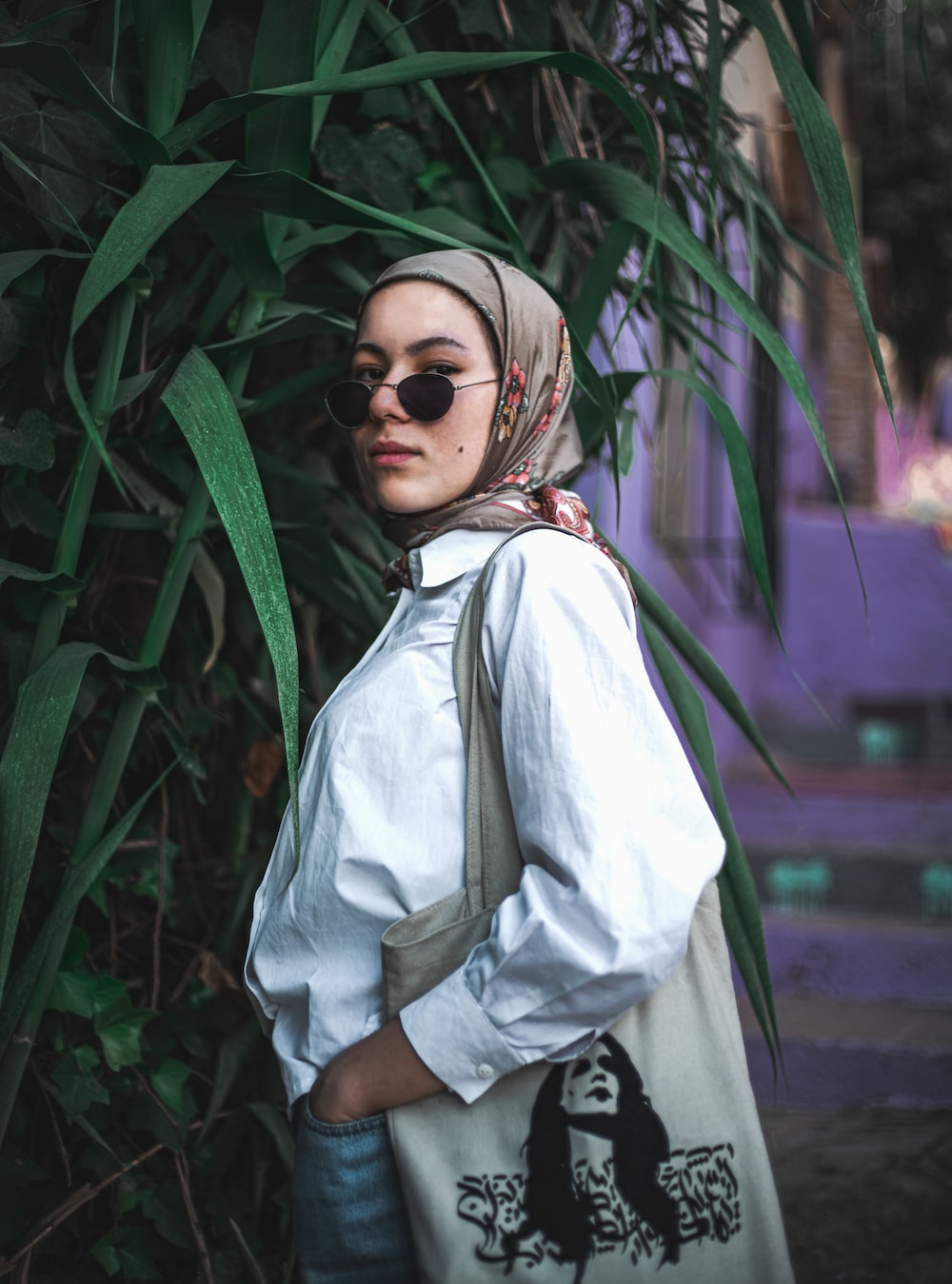 woman in white hijab standing near green plant