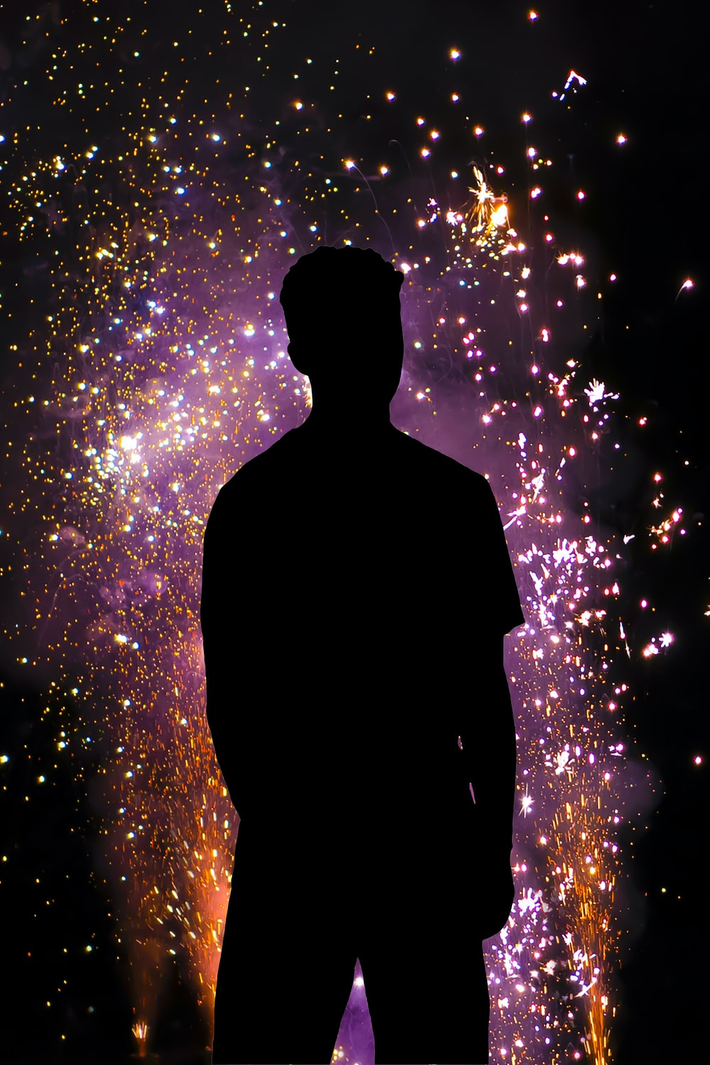 silhouette of man standing under fireworks