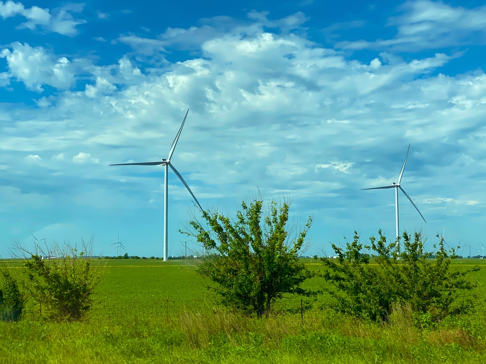 wind turbines on green grass field under blue and white cloudy sky during daytime