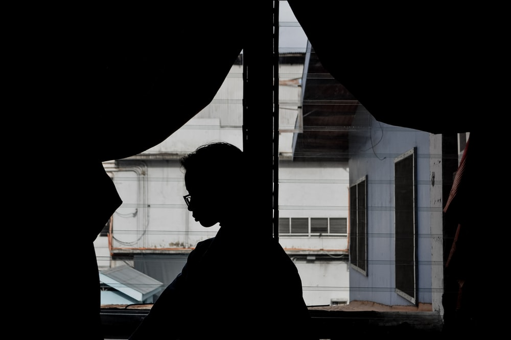 silhouette of person standing near window during daytime