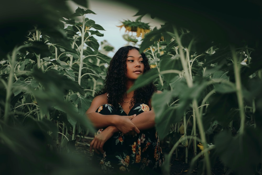 woman in black and brown floral dress standing in the middle of green plants