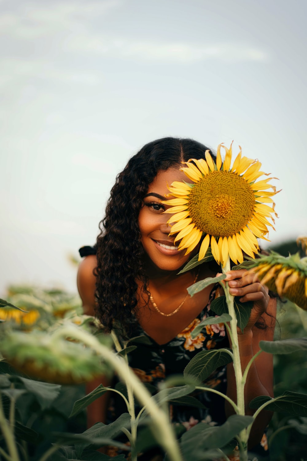 woman in black and green floral dress holding sunflower