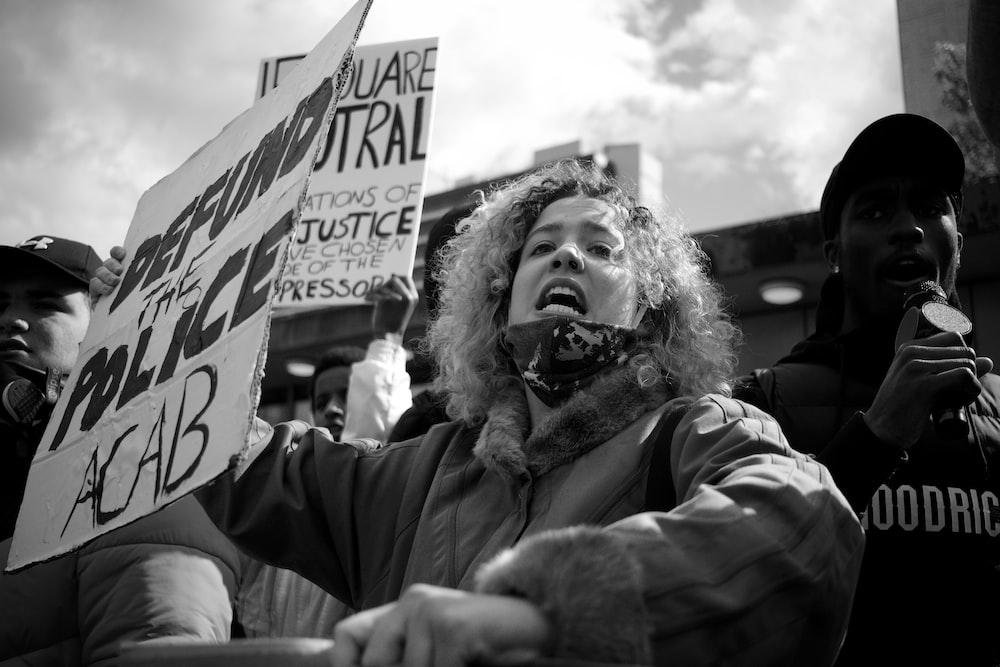 grayscale photo of girl holding signage