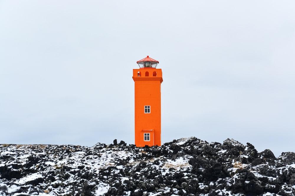orange and white lighthouse on rocky ground under gray sky