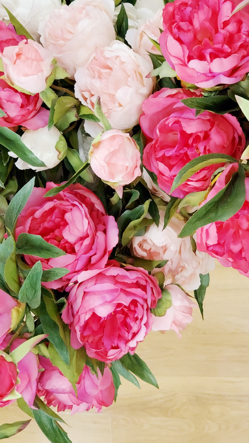 pink and white roses on brown wooden table