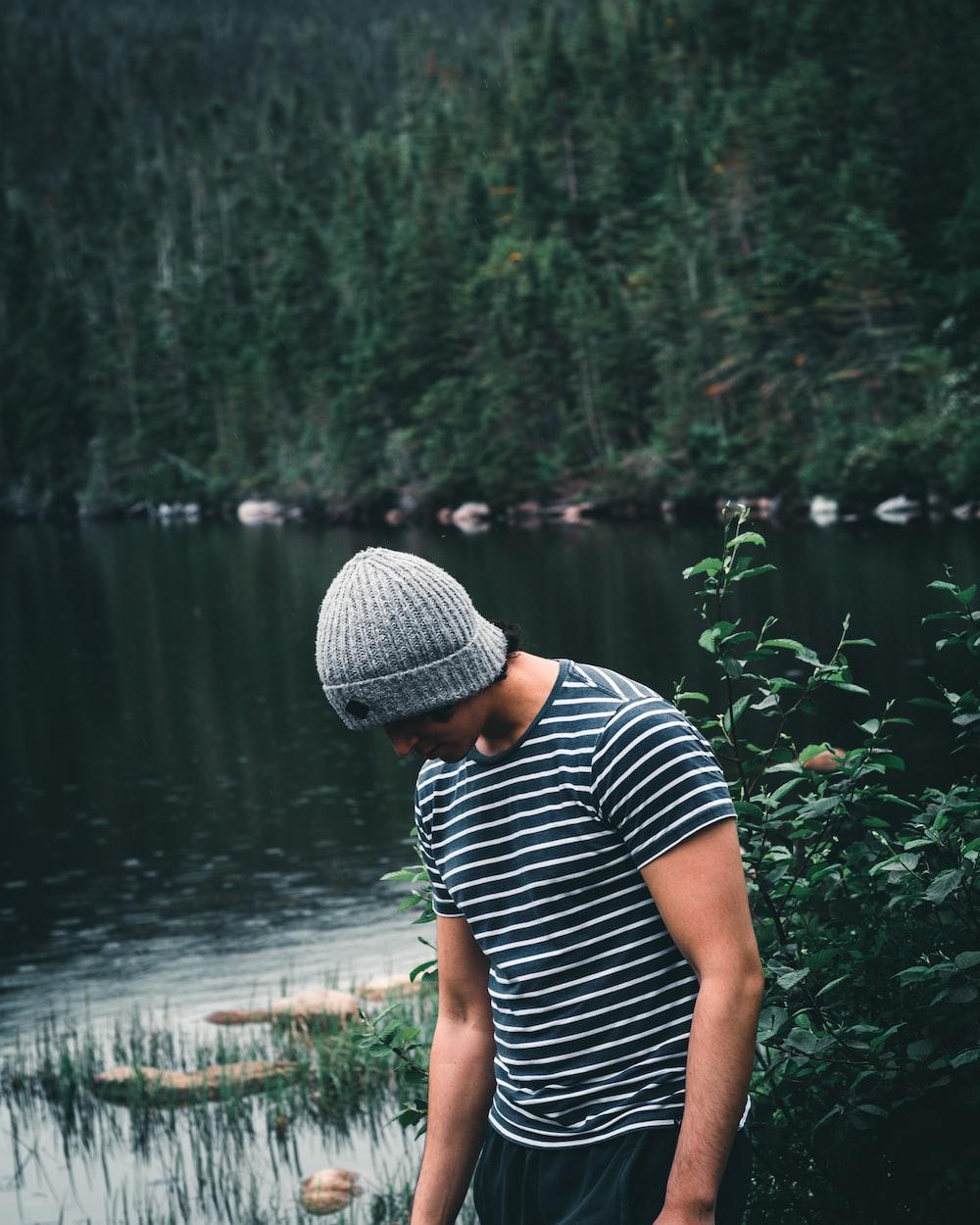 woman in black and white stripe shirt standing near lake during daytime