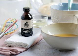 white ceramic bowl beside black glass bottle