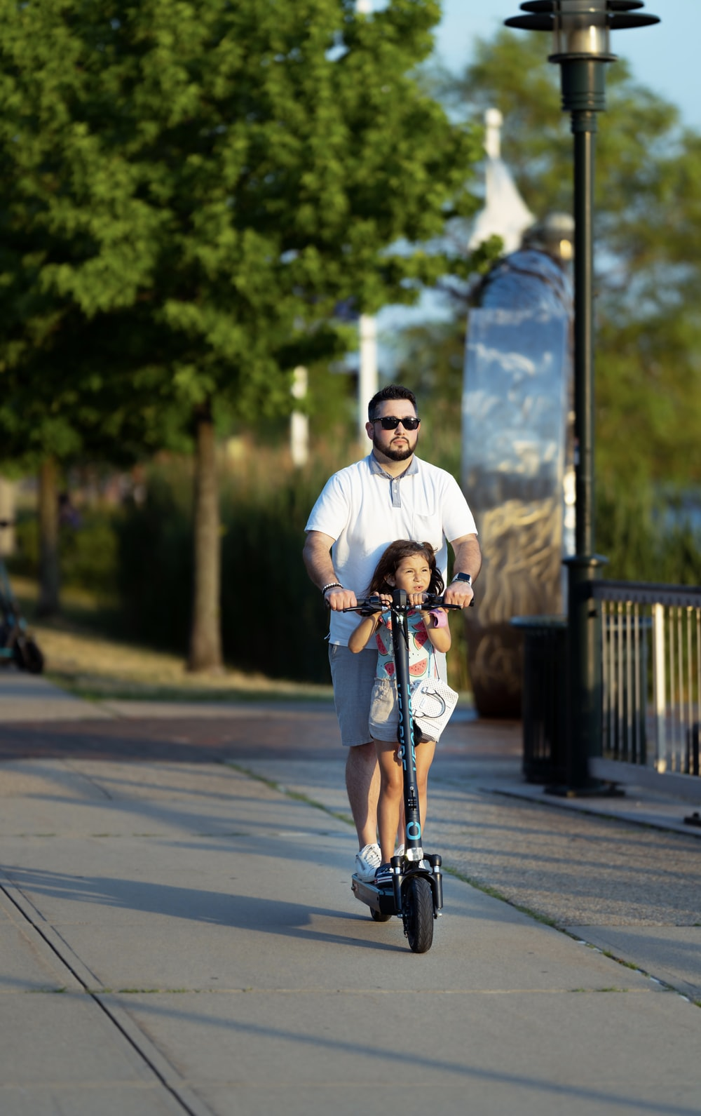man in white crew neck t-shirt and blue denim shorts riding on black kick scooter