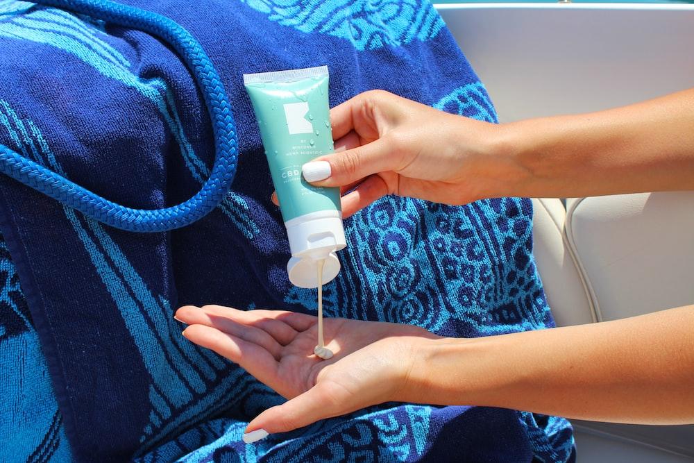 person holding white plastic tube bottle