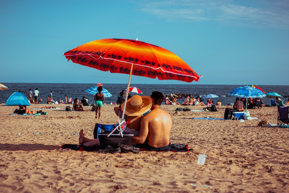 man sitting on blue and white chair under orange umbrella on beach during daytime