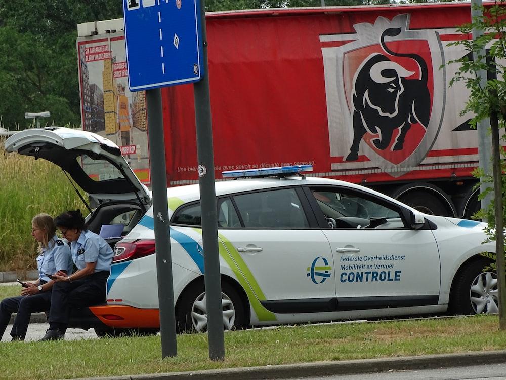 man in black jacket sitting on white car