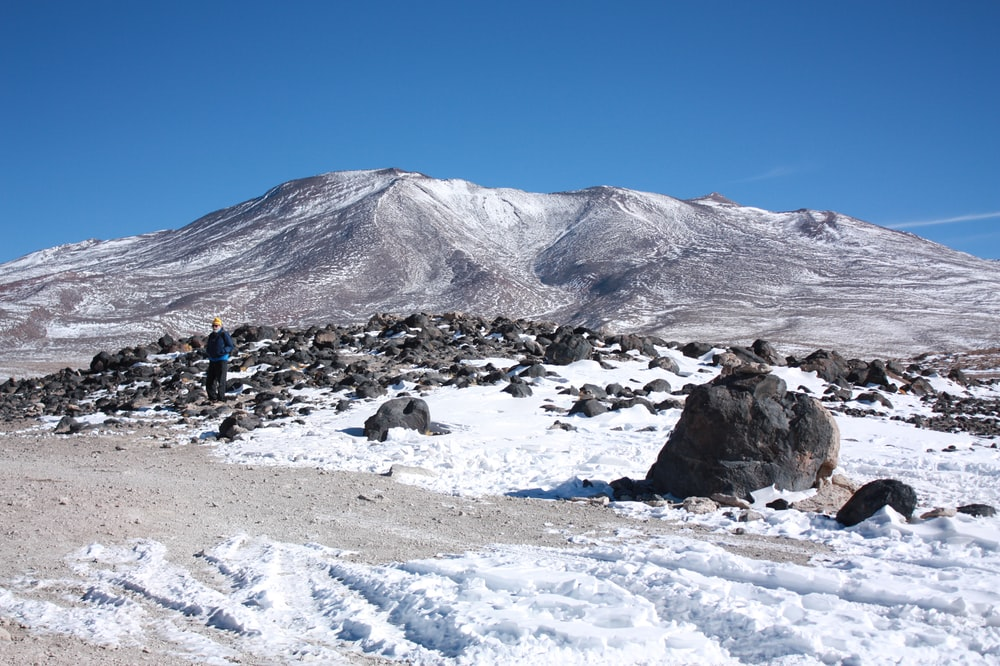 people on snow covered field near mountain under blue sky during daytime