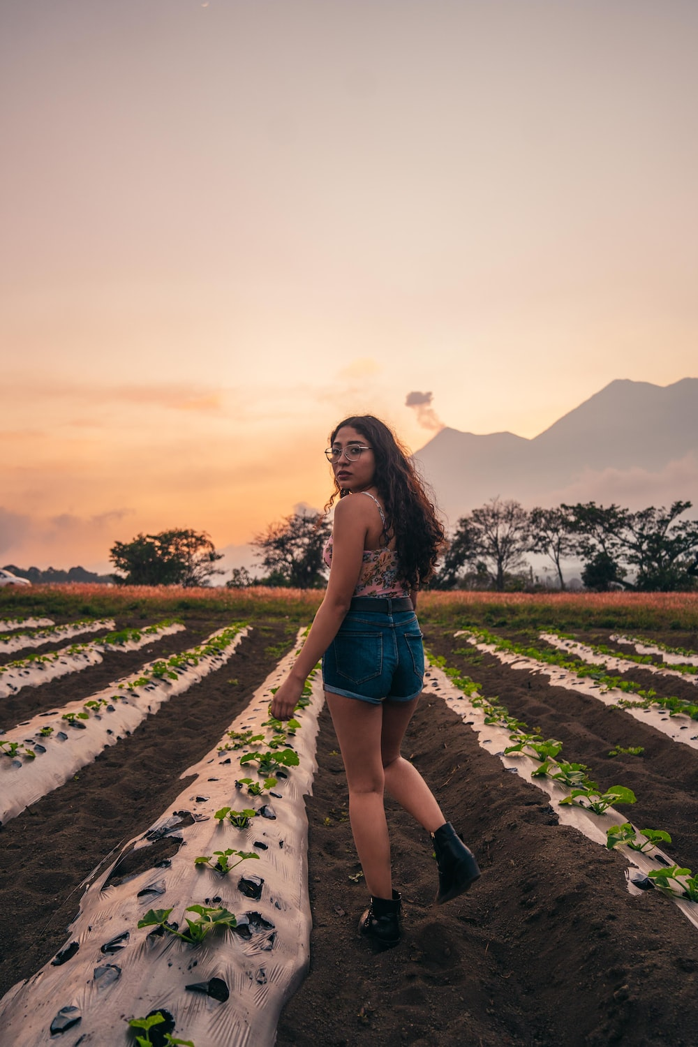 woman in blue denim shorts standing on green grass field during sunset