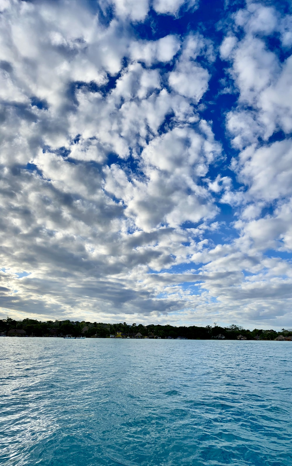 body of water under blue sky and white clouds during daytime