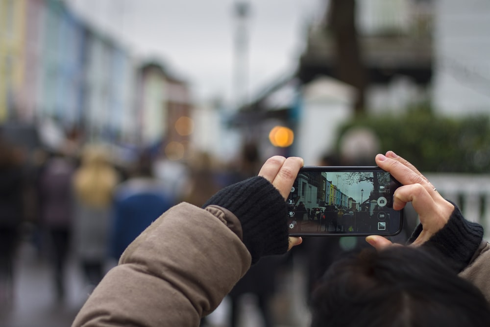 person holding black smartphone taking photo of people during daytime