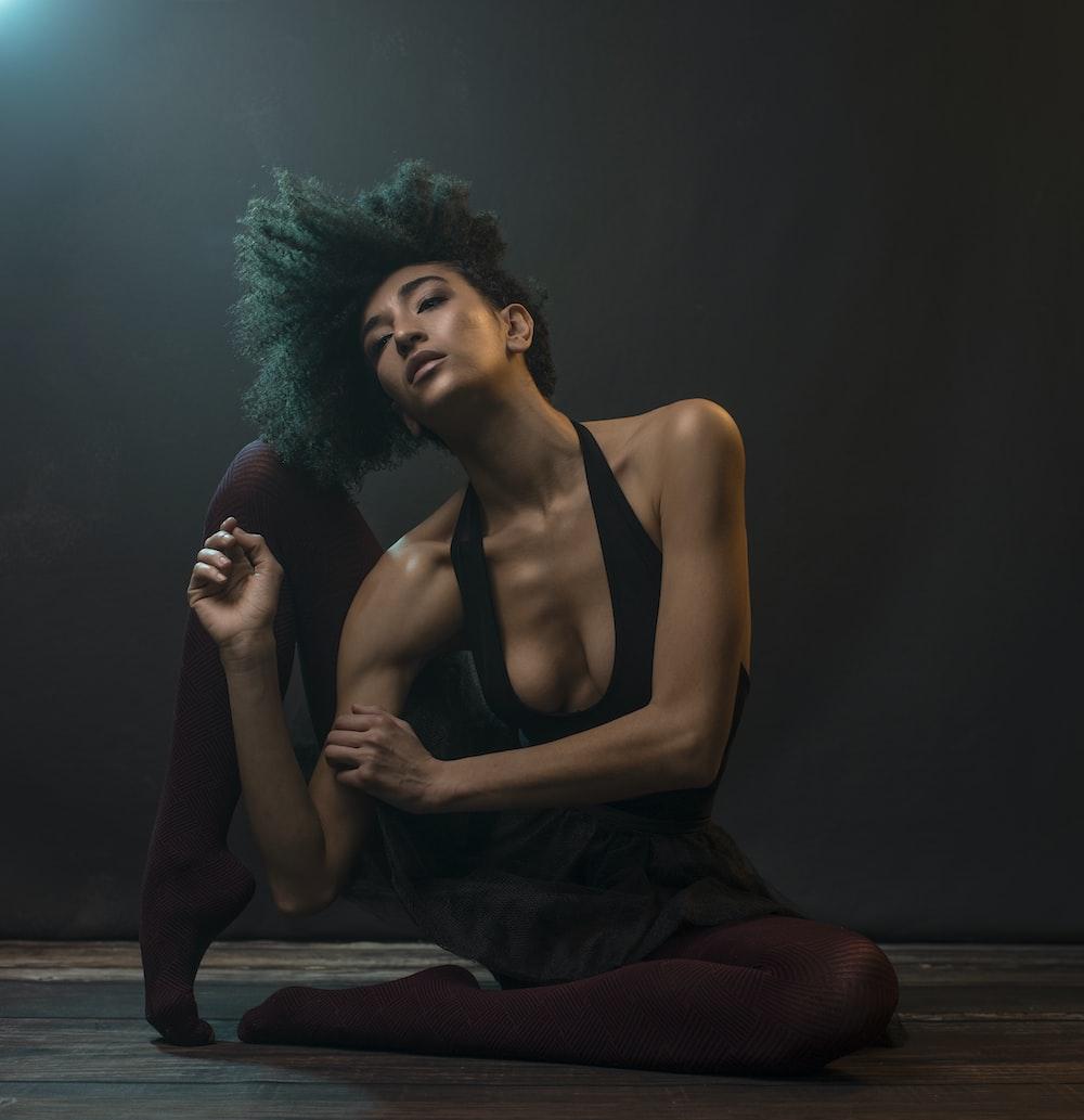 woman in black tank top sitting on floor