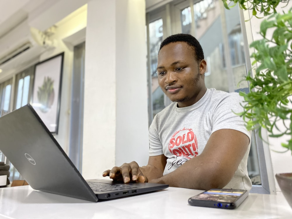 man in white and red crew neck t-shirt using laptop computer