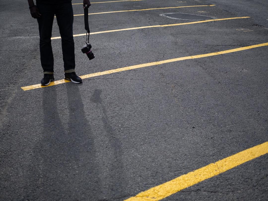Person In Black Pants Walking On Gray Asphalt Road - unsplash