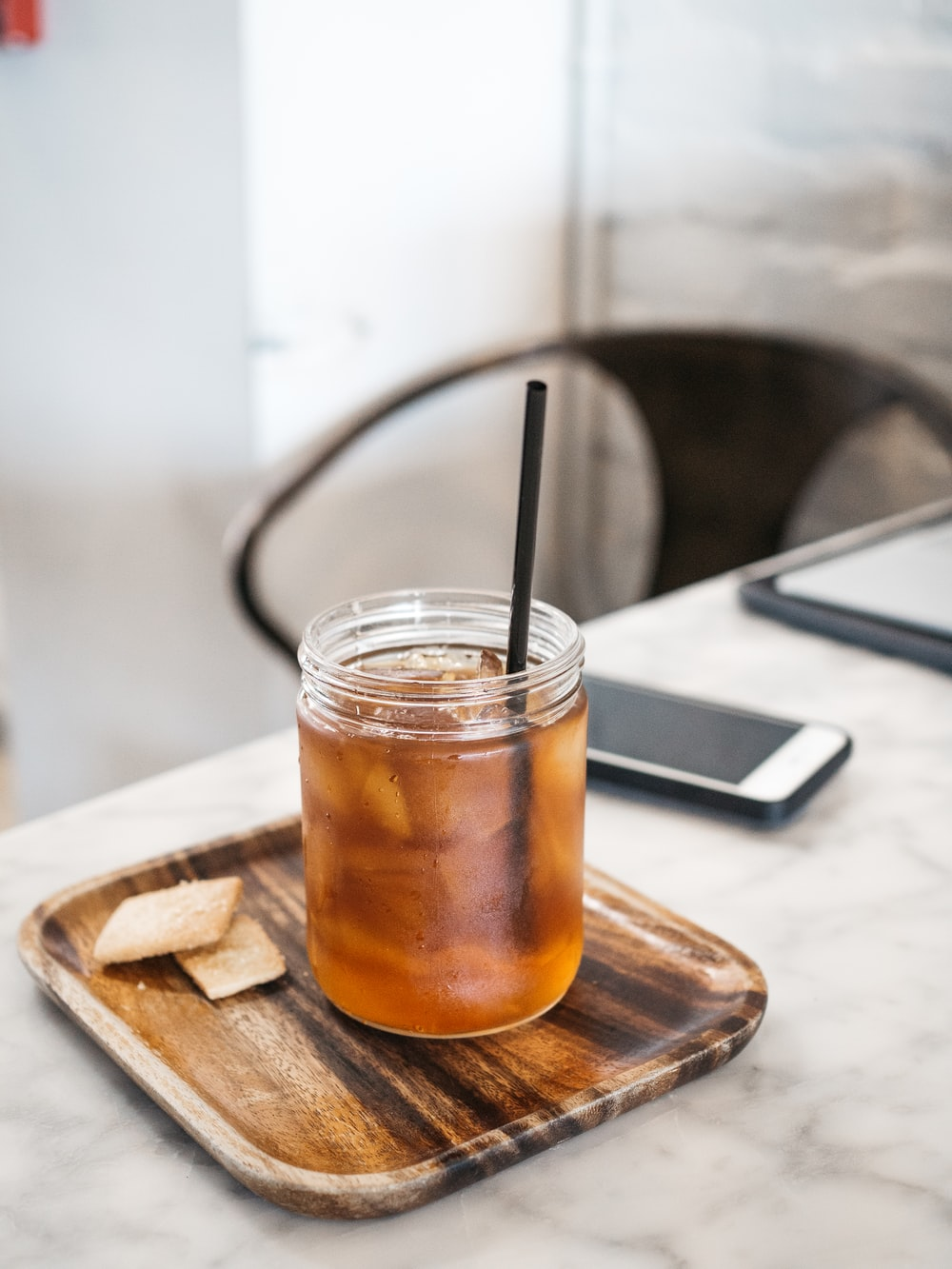clear drinking glass with brown liquid on brown wooden coaster