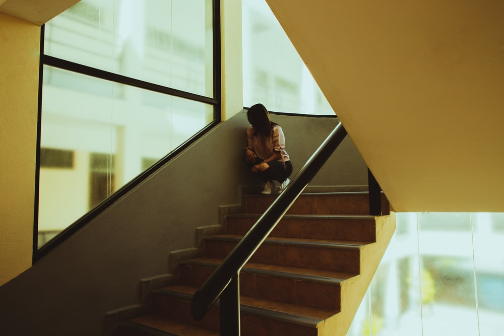woman in black jacket sitting on brown staircase