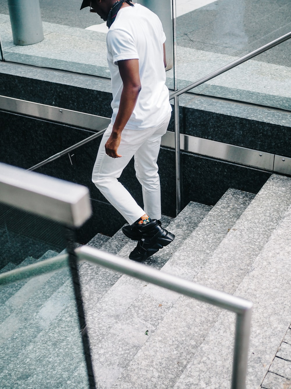man in white pants and black shoes walking on gray concrete pavement