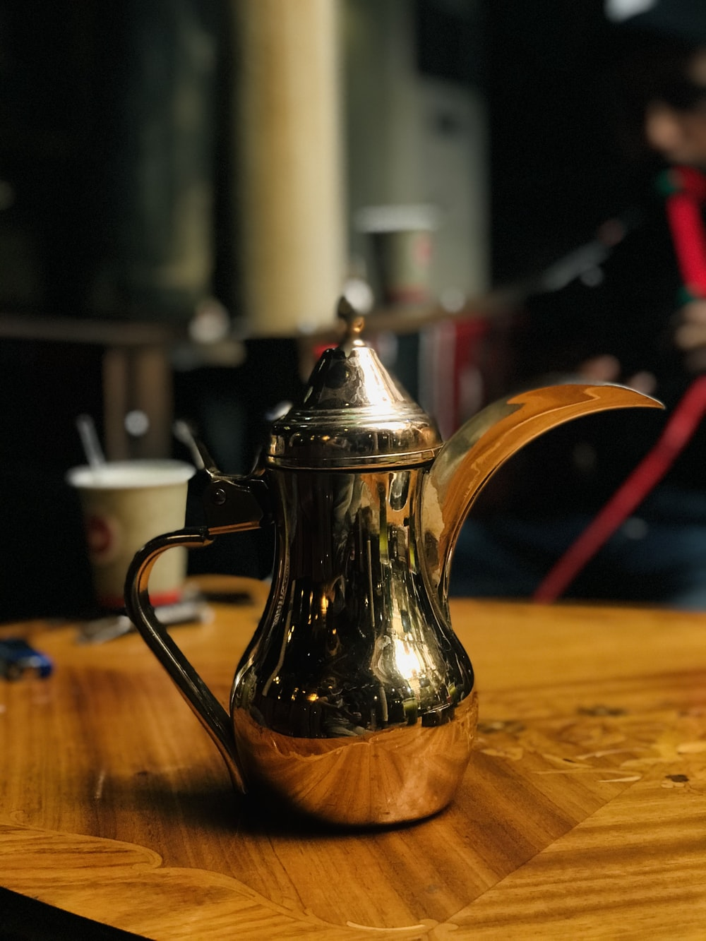 stainless steel teapot on brown wooden table
