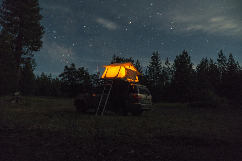 black car parked beside tent under starry night