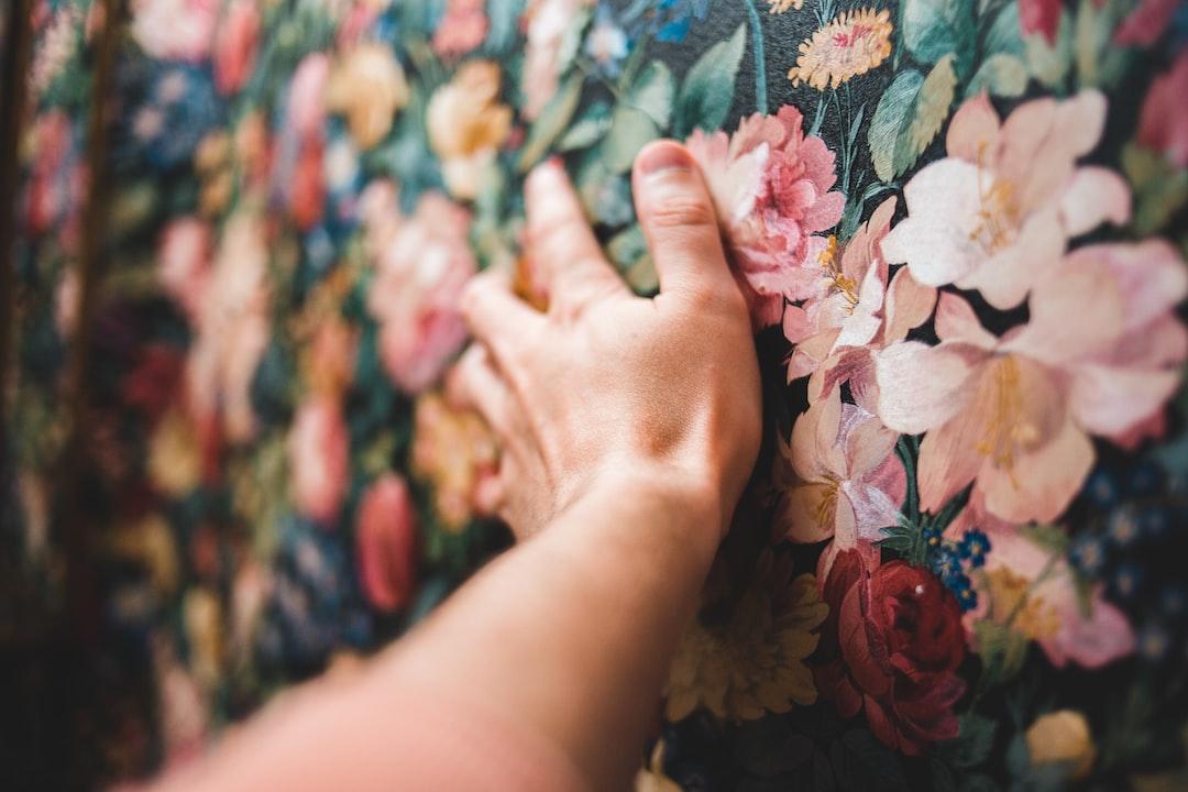 Persons Hand On Floral Textile - unsplash