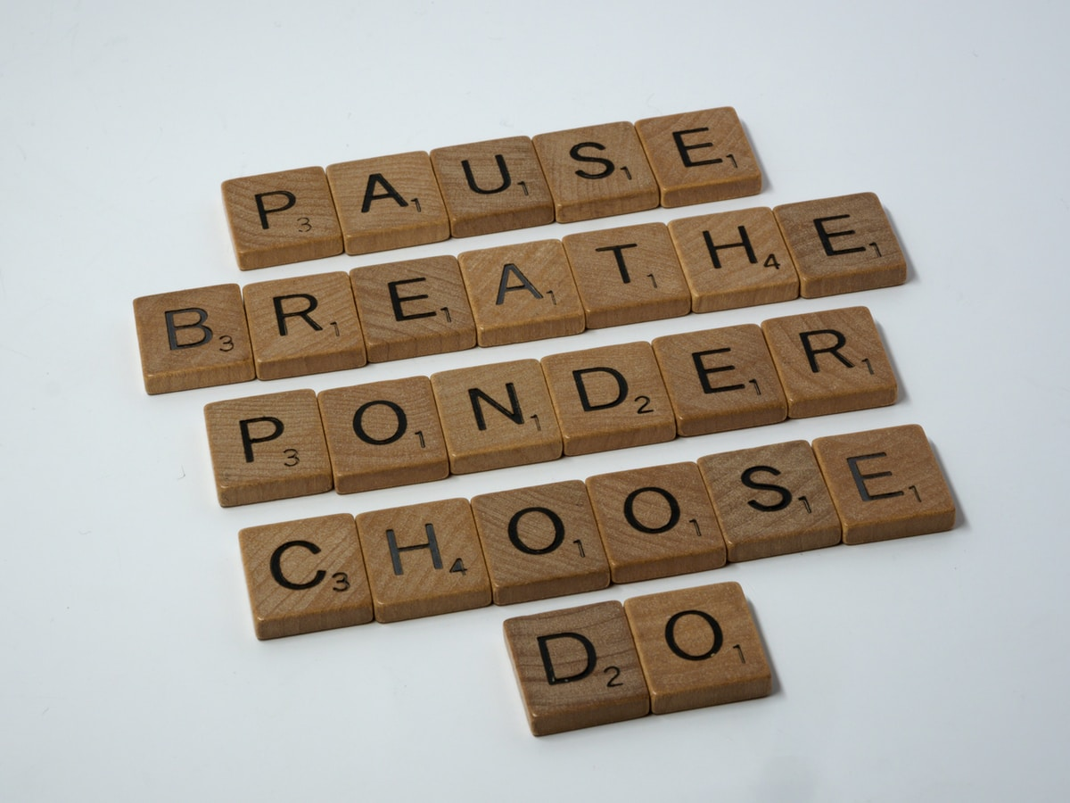 Words made up of scrabble tiles vertically arranged on a white background - pause, breathe, ponder, choose, do