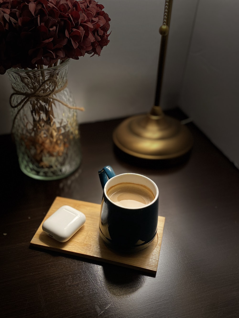 white ceramic mug on black saucer beside red flowers