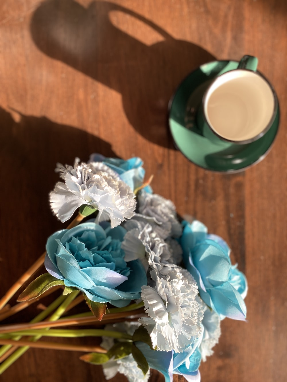 blue and white flower bouquet beside green ceramic mug on brown wooden table