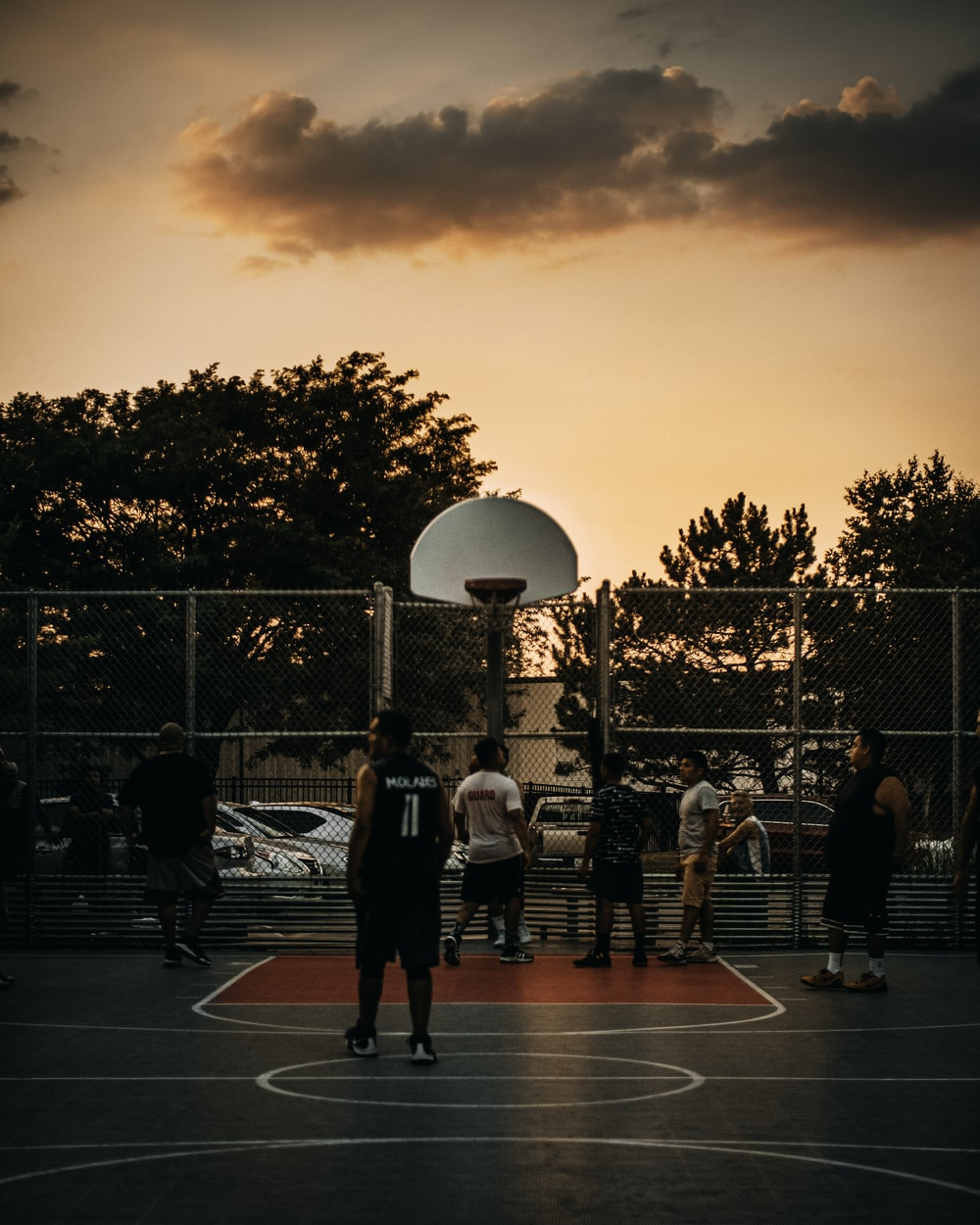 people playing basketball on court during sunset
