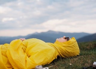 man in yellow hoodie lying on green grass field under white cloudy sky during daytime