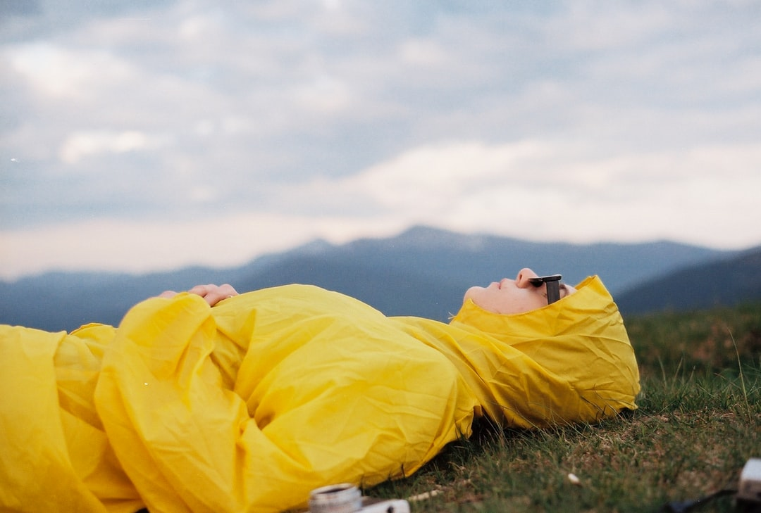 Man In Yellow Hoodie Lying On Green Grass Field Under White Cloudy Sky During Daytime - unsplash