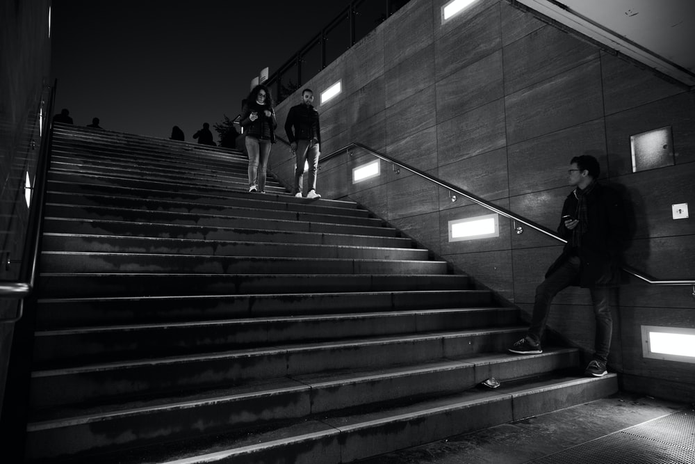 grayscale photo of man in black t-shirt and pants walking on stairs
