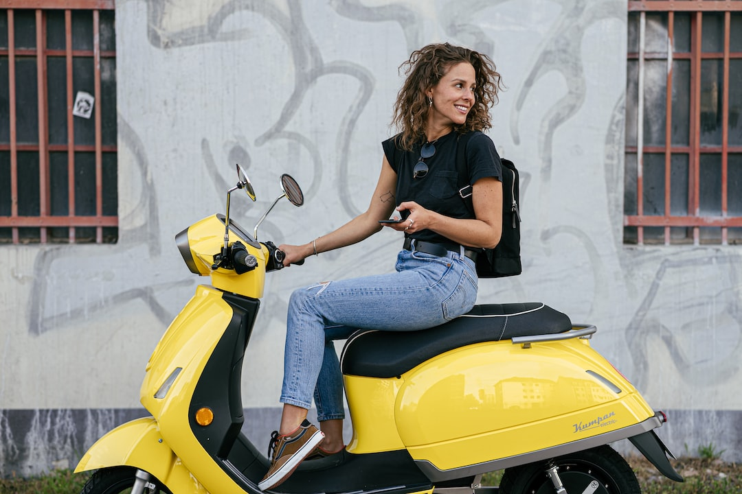 A Young Woman Sitting On Her Eco-Friendly, Electrically Driven Scooter Kumpan 54 Iconic. - unsplash