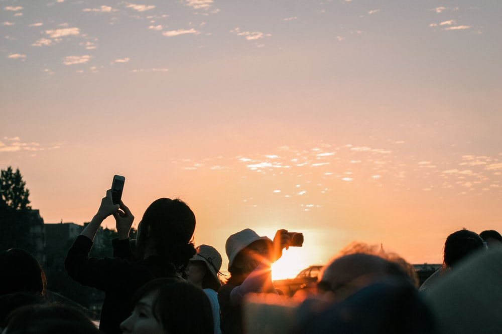 silhouette of people taking photo of sunset